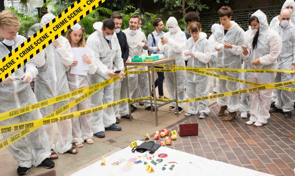People dressed in protective clothing at a crime scene