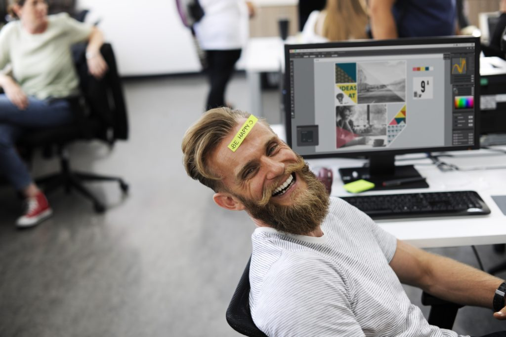 Man smiling in the workplace with a sticker on his head
